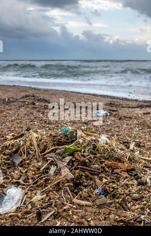 Spilled garbage on the beach of the big city. Empty used dirty plastic bottles. Dirty sea sandy shore. Environmental pollution. Ecological problem. Bo - Stock Photo