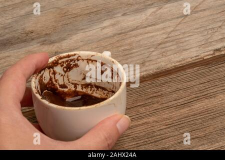 female hand holding a cup of coffee in order to fortune telling