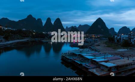 Dawn's early light on the Li River with tour boats, Yangshuo, Guangxi Province, China - Stock Photo