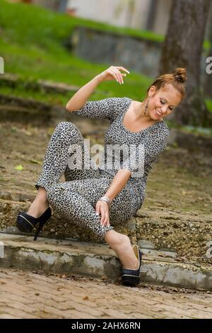 Checking her herself heel in high-heeled high-heels highheels spiked spike stiletto stilettos shoes looking down smiling - Stock Photo