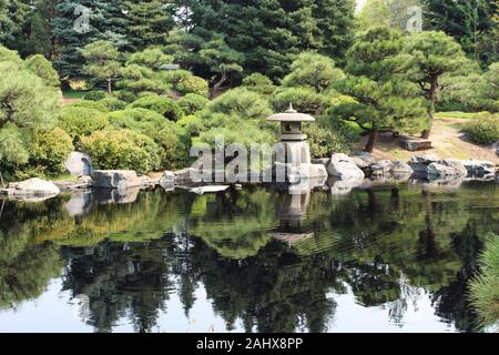 A Japanese style garden with a stone lantern and various cultivated evergreen trees next to a lake, with the landscape reflected in the water in Color
