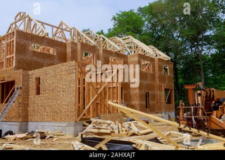 Framing beam of new house boom truck forklift in the under construction home beam construction - Stock Photo