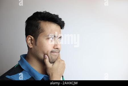 right side face of an asian man with inquisitive expression looking towards a copy space with white background - Stock Photo