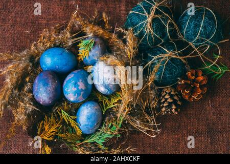 space galactic Easter eggs in nest next to cone and green filler - Stock Photo