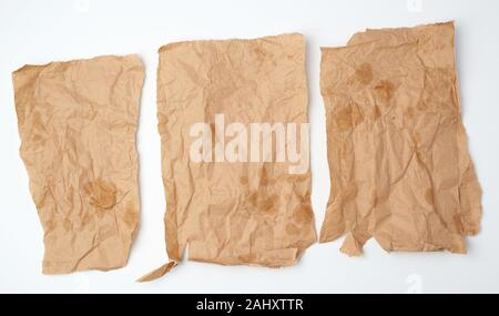 three torn crumpled pieces of brown paper with grease stains on a white background, top view. - Stock Photo
