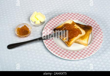Spread jam on bread with knife. - Stock Photo