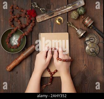 two hands in a prayer pose on a wooden brown table in the middle of vintage Tibetan meditation tools, alternative medicine, top view. - Stock Photo