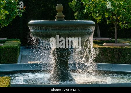 Sprinkling water of a fountain with detailed water drops glinstering in bright sunshine in Berlin-Marzahn, Germany. - Stock Photo