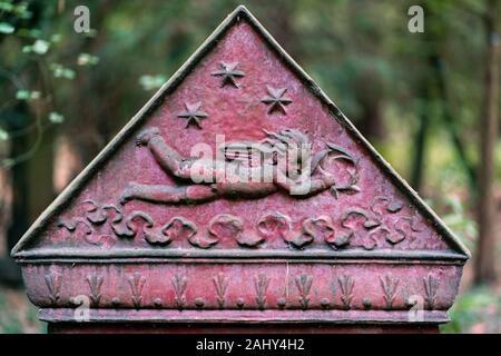 Triangular part of a tombstone showing a flying cherub on red background with stars in the sky at Suedwestfriedhof cemetery, Stahnsdorf, Germany - Stock Photo