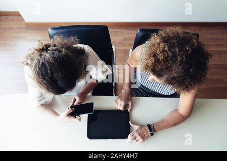 Two businesswomen working together at office. Top view.