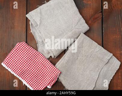 white red checkered kitchen towel and gray linen napkins on a brown wooden background, picnic background, copy space. - Stock Photo