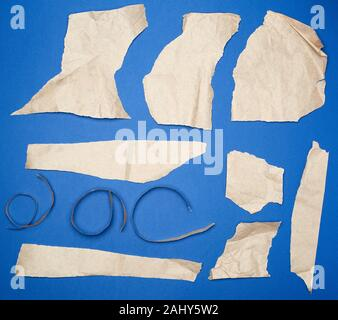 set of various pieces of torn brown crumpled paper on a blue background, close up. - Stock Photo