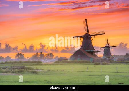 Traditional village with dutch windmills and river at sunset, Holland, Netherlands. - Stock Photo