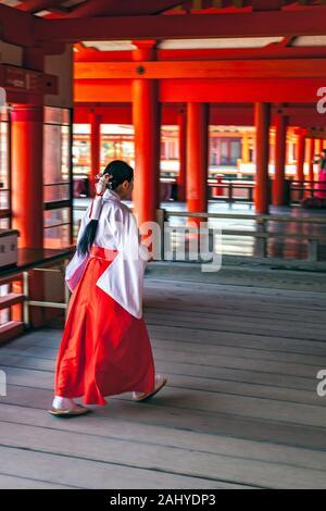 A Shinto priest in the 16th-century Shinto Itsukushima Shrine, Miyajima, Ono Sotoki, Hiroshima Ken, Japan. - Stock Photo