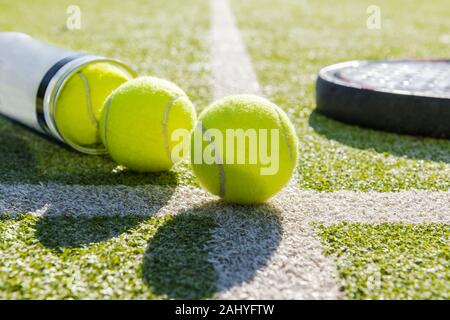 paddle tennis racket and tube with balls on court of artificial turf, indoor sports concept and sporty lifestyle - Stock Photo