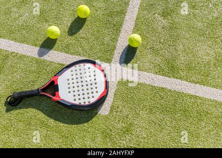 top view of a paddle tennis racket and balls on court of artificial grass, indoor sports concept and sporty lifestyle - Stock Photo