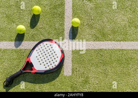 top view of a paddle tennis racket and balls on court of artificial turf, indoor sports concept and sporty lifestyle - Stock Photo
