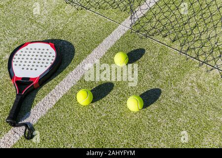 paddle tennis racket, balls and net on court of artificial turf, indoor sports concept and sporty lifestyle - Stock Photo