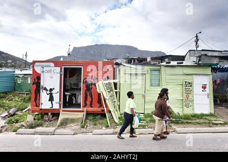 South Africa: Imizamo Yethu township in the suburbs of Hout Bay, near Cape Town, Western Cape. Women walking in a street and Community Cell phone shop