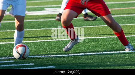 High school soccer players legs fighting for the soccer ball on a green turf field. - Stock Photo