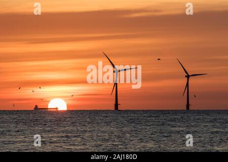 Solar energy and wind power. Climate change and global warming. Offshore windfarm turbines silhouetted by the rising sun with industry in the form of