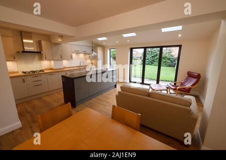 A modern open plan kitchen dining living room rear extension to a property in Chester with bifold doors and velds skylights - Stock Photo