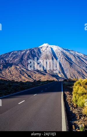 Spain, Tenerife, Black asphalt road alongside lava fields to famous white snow covered peak of mount teide volcano with blue sky - Stock Photo