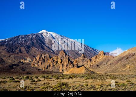 Spain, Tenerife, Dry caldera desert nature landscape, green plants at impressive mountain volcano teide, peak covered by white snow in winter - Stock Photo
