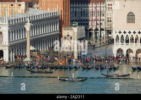 Elevated view of a busy St. Mark's Square in Venice during high tide with gondolas lined up along the shore, Venice, UNESCO, Veneto, Italy - Stock Photo