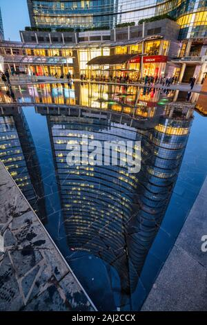 Milan Italy, Porta Nuova District. Gae Aulenti Square. Unicredit Tower reflected in a puddle - Stock Photo