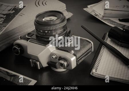 Desk of a traveler of the last century in retro style. Next to the metal camera is an old photo album, photographs, film and a notebook. - Stock Photo