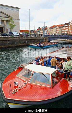 Sightseeing tour boats on a Slotsholmen canal and  Gammel Strand street lined by a row of brightly coloured old houses in downtown Copenhagen,Denmark