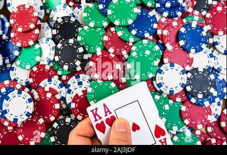 Poker hand over poker chips background. Casino concept for business, risk, chance, good luck or gambling - Stock Photo