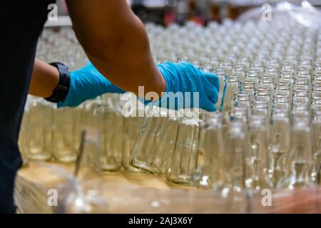 a lot of new beer white glass empty bottle, person hands with blue Rubber glove holding bottles, selective focus close up view - Stock Photo