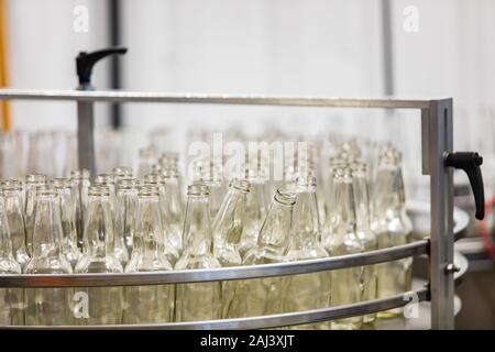 a lot of new white glass empty beer bottles on machine, selective focus close up view, conveyor belt craft brewery factory microbrewery - Stock Photo