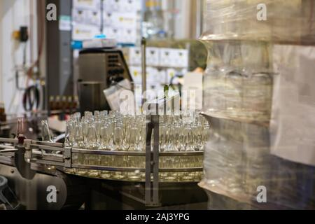 white glass empty beer bottles selective focus, on conveyor belt system machine, craft brewery factory microbrewery bottling warehouse - Stock Photo