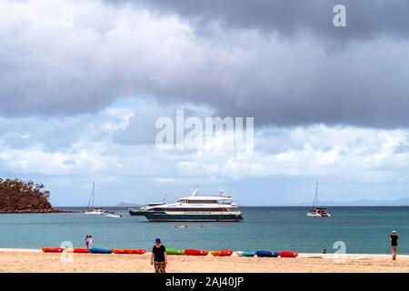 Yeppoon, Queensland, Australia - December 2019: Tourists walk on the beach and paddle kayaks in front of a tourist boat anchored at Great Keppel Islan - Stock Photo
