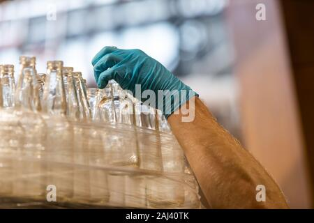 a lot of new beer white glass empty bottles, caucasian man hand with blue Rubber glove holding one bottle, selective focus close up view - Stock Photo