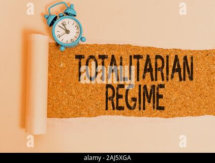 Writing note showing Totalitarian Regime. Business concept for mode of government that prohibits opposition parties Alarm clock and torn cardboard on - Stock Photo