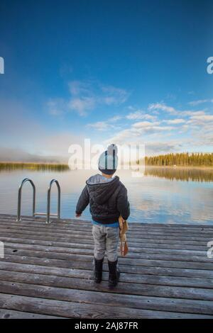 Young boy standing on wooden dock at the lake. - Stock Photo