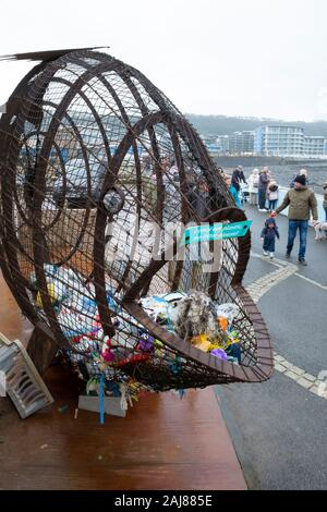 Filup The Fish, created by metal artist Robert Floyd, for plastic waste bottle collection on the promenade at Westward Ho! North Devon, UK - Stock Photo