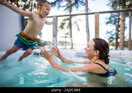Young boy jumping into swimming pool, mom waiting to catch him. - Stock Photo