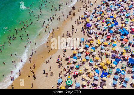 Rio de Janeiro, Brazil, aerial view of Copacabana Beach showing colourful umbrellas and people bathing in the ocean on a summer day.