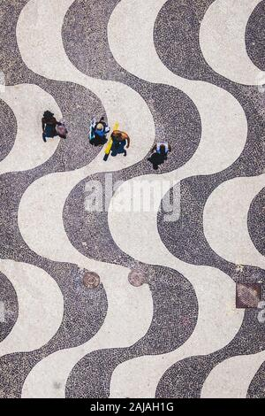 Rio de Janeiro, Brazil, top aerial view of people walking on the iconic Copacabana Beach mosaic sidewalk. - Stock Photo