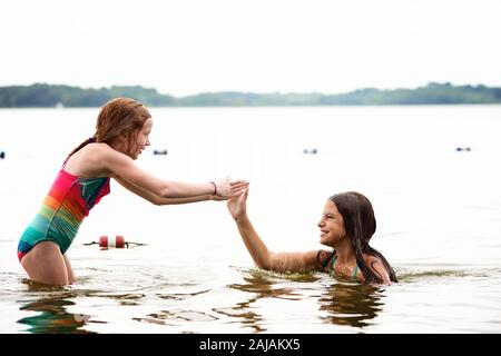 Two Young Girls in Swimsuits Playing in a Lake - Stock Photo