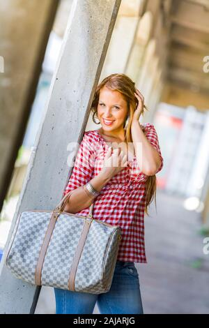 Standing leaning inclined on concrete post hand touching touch hair head giggling - Stock Photo