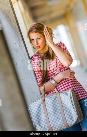 Standing leaning inclined on concrete post hand touching touch hair head - Stock Photo