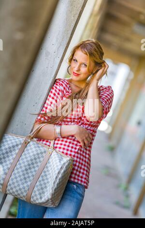Standing leaning inclined on concrete post hand touching touch hair head with slight smile - Stock Photo