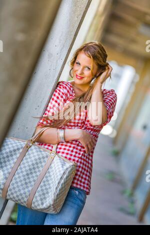 Standing leaning inclined on concrete post hand touching touch hair head smile smiling - Stock Photo