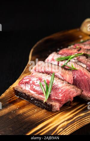 Juicy Beef Rib Eye Steak slices slightly salted, with herbs and spices on wooden board. Fresh grilled meat. Dark black background - Stock Photo